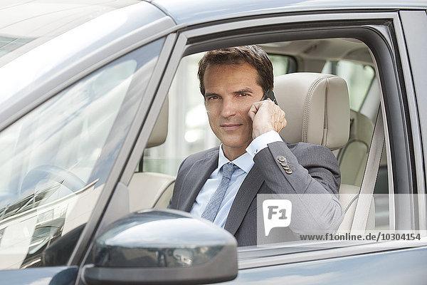 Geschäftsmann mit Handy beim Autofahren