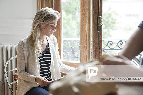Junge Frau beim Lesen am Fenster sitzend