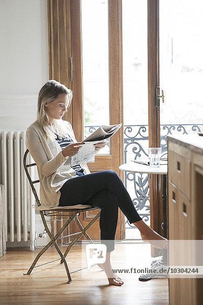 Junge Frau beim Zeitungslesen zu Hause