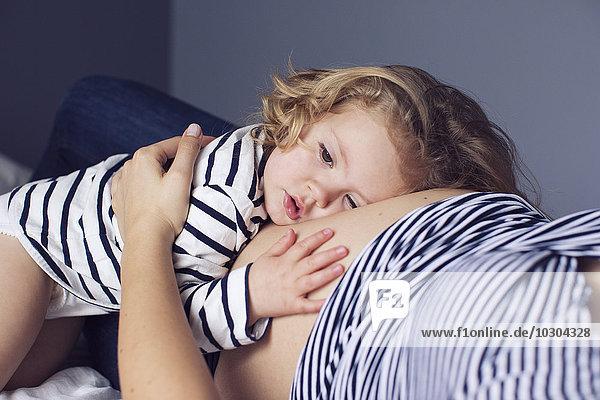 Kleines Mädchen  das den Kopf und die Hand auf den schwangeren Bauch der Mutter legt.