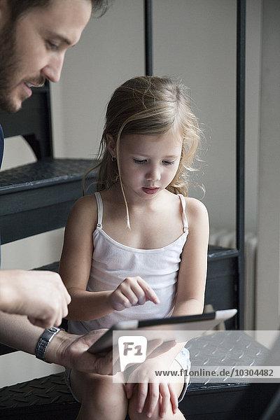 Vater zeigt der jungen Tochter  wie man ein digitales Tablett benutzt.