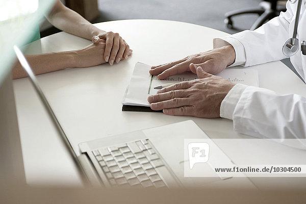 Arzt präsentiert dem Patienten die Testergebnisse