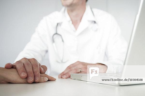 Arzt  der den Patienten während der Sprechstunde betreut