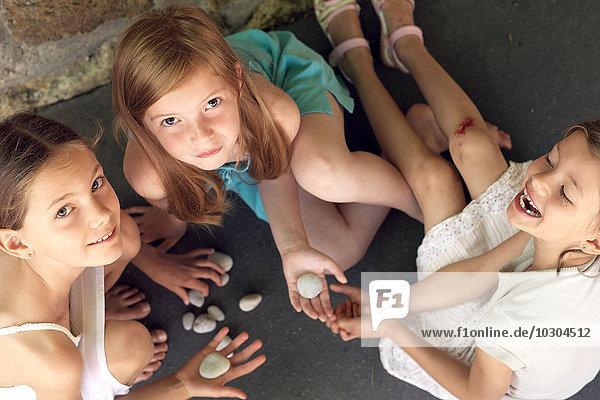 Mädchen sitzen zusammen und spielen mit Kieselsteinen.