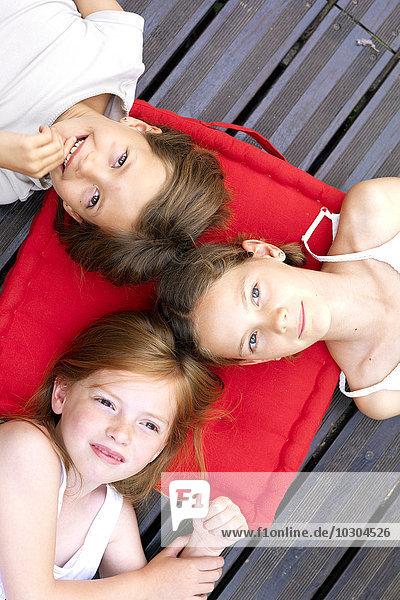 Mädchen im Freien liegend mit Köpfen auf einem gemeinsamen Kissen