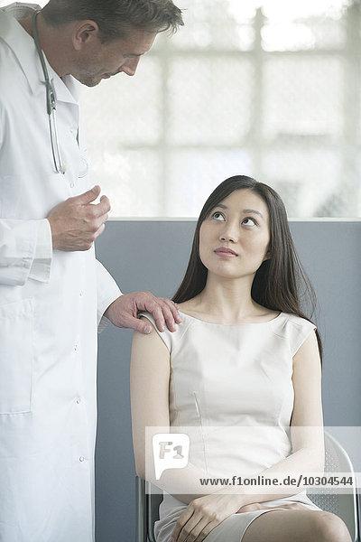 Arzt im Gespräch mit dem Patienten im Wartezimmer