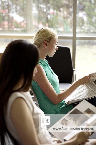 Frauen  die lesen  um die Zeit im Wartezimmer zu vertreiben.