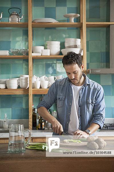Mann schneidet Zutaten in der Küche