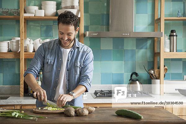 Mann zerkleinert frische Zutaten in der Küche