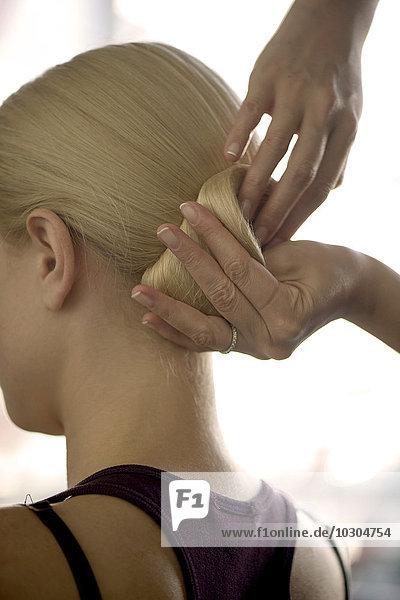 Friseur arrangiert Frauenhaar in einem Chignon  geschnitten
