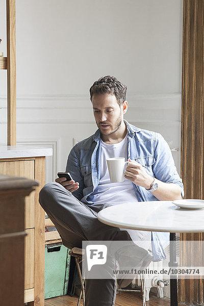 Mann sendet SMS während der Kaffeepause