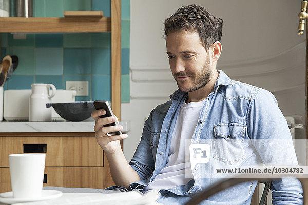 Mann liest Nachrichten auf dem Smartphone während des Frühstücks