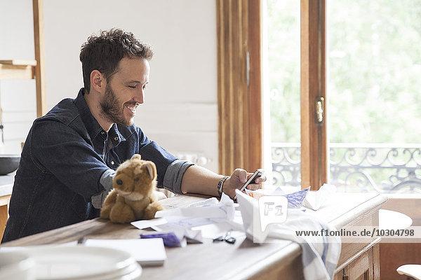 Mann zu Hause mit Smartphone