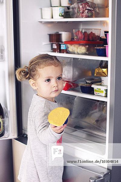 Kleines Mädchen  das Essen aus dem Kühlschrank holt. Kleines Mädchen, das Essen aus dem Kühlschrank holt.