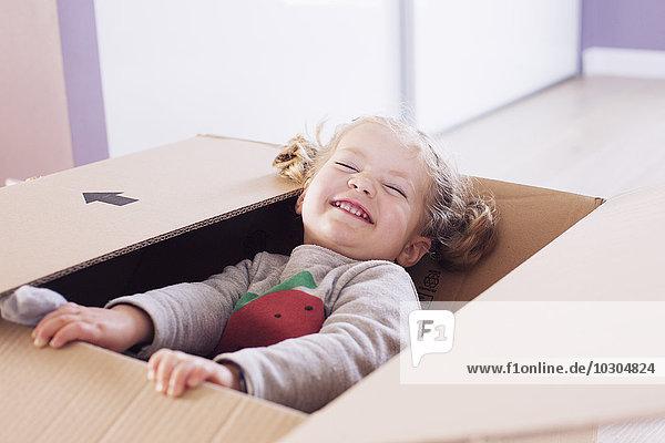 Kleines Mädchen spielt im Karton  Portrait
