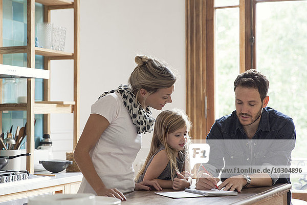 Vater hilft der kleinen Tochter beim Unterricht