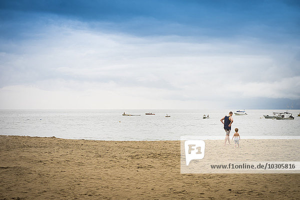 Mexico  man with toddler boy walking on the beach