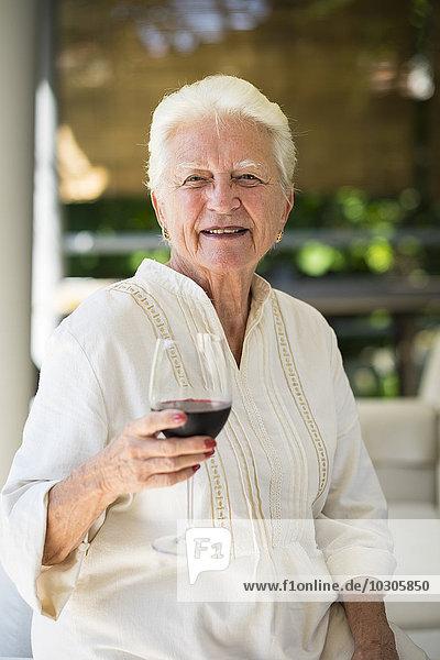 Porträt einer lächelnden Seniorin mit einem Glas Rotwein