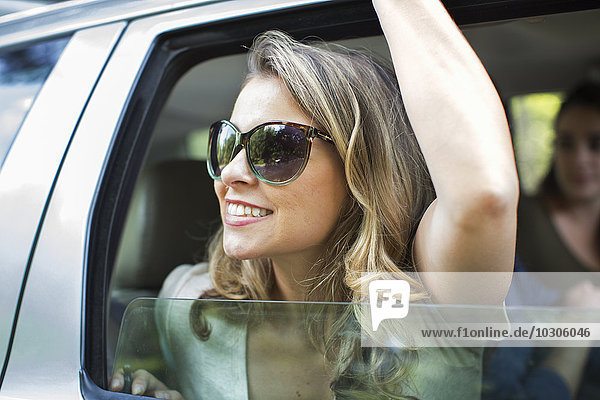 A young woman leaning out of a car window with her arm raised.