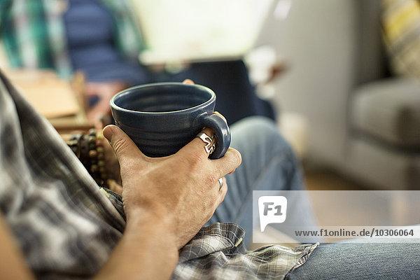 Eine Person  die einen großen schwarzen Porzellanbecher hält und auf einem Stuhl sitzt.