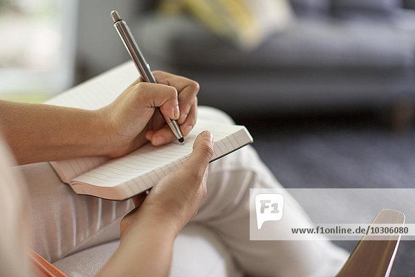 Eine sitzende Frau hält ein offenes Tagebuch und einen Stift in der Hand.