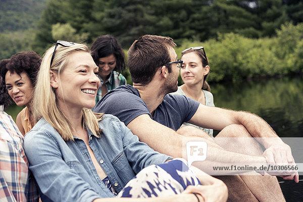 Eine Gruppe von Frauen und Männern saß auf einem Steg an einem See auf dem Land.