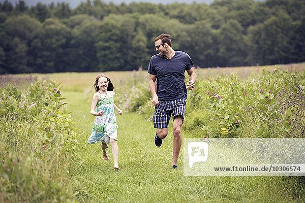 Ein Mann und ein kleines Kind rennen durch eine Wildblumenwiese.