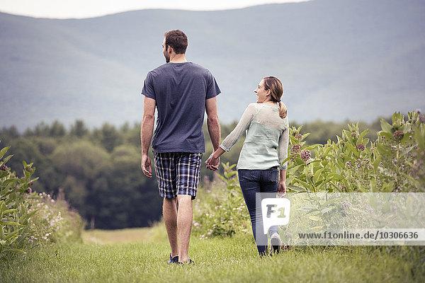 Ein Paar  ein Mann und eine Frau gehen durch eine Wiese und halten sich an den Händen.