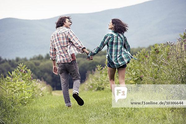 Ein Paar  Mann und Frau  die Hand in Hand durch eine Wiese laufen.