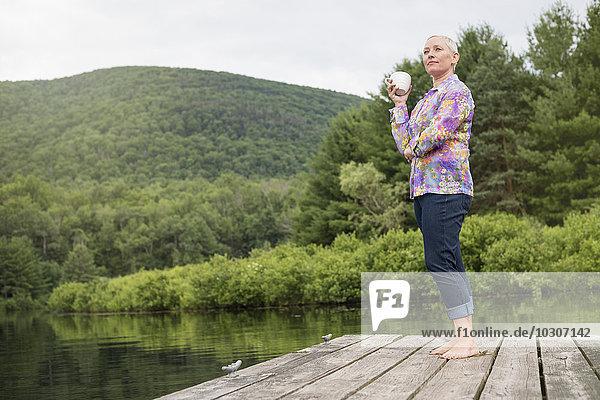 Eine Frau steht auf einem Dock am See und hält eine Kaffeetasse.