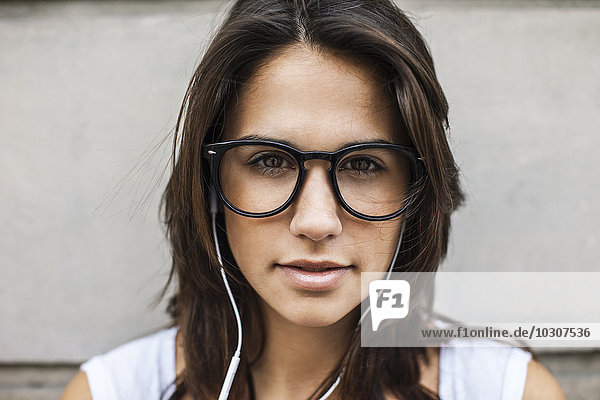 Portrait of young woman with ear phones wearing black glasses