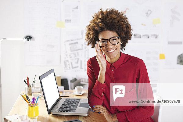 Porträt einer lächelnden jungen Architektin mit Laptop am Schreibtisch