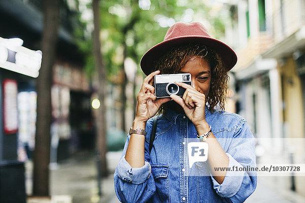 Spanien  Barcelona  Porträt einer lächelnden jungen Frau mit Hut und Jeanshemd  die mit der Kamera fotografiert.