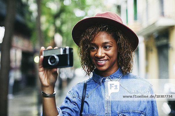 Porträt einer lächelnden jungen Frau mit Hut und Jeanshemd mit Kamera