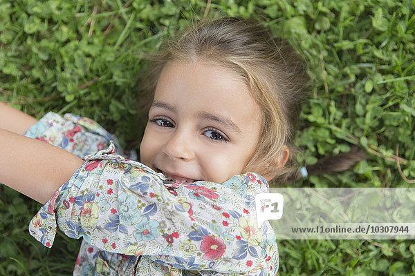 Portrait of smiling little girl lying on a meadow