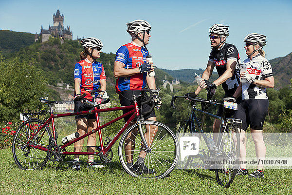 Germany  Rhineland-Palatinate  US American couples standing in nature in front of Eltz Castle with their tandems