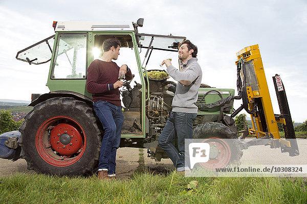 Deutschland  Bayern  Volkach  zwei Winzer verkosten Weißwein am Traktor