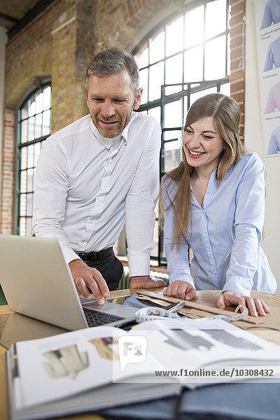 Reifer Mann und junge Frau arbeiten in der Schneiderei zusammen.