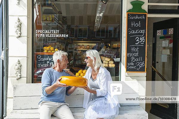 Niederlande  Amsterdam  Seniorenpaar auf der Bank sitzend mit Käsebrot