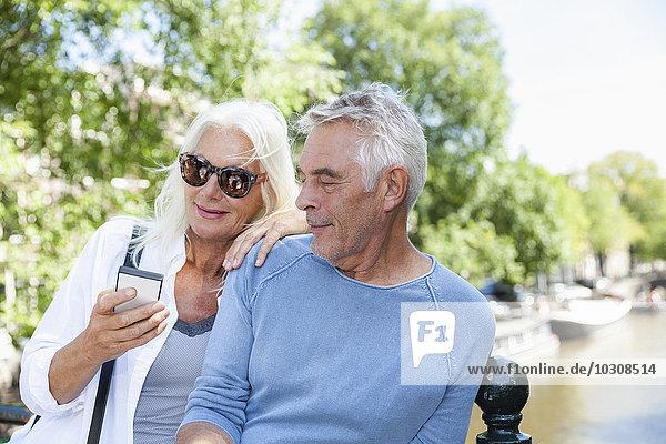Niederlande  Amsterdam  Seniorenpaar mit Handy am Stadtkanal