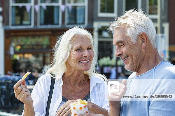 Niederlande  Amsterdam  glückliches Seniorenpaar beim Pommes Frites essen