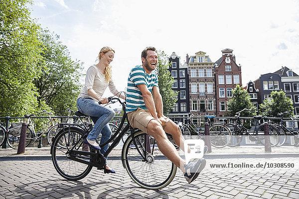 Niederlande  Amsterdam  glückliches Paar beim Fahrradfahren in der Stadt