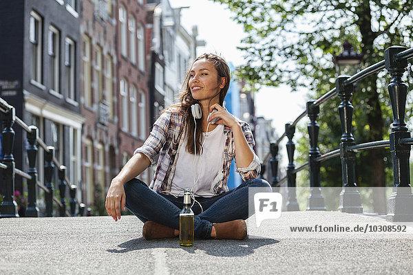 Niederlande  Amsterdam  junge Frau sitzend mit Kopfhörer und Bierflasche auf Brücke