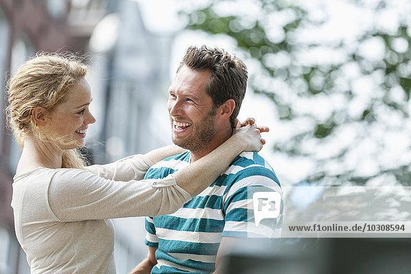 Lächelndes Paar  das sich im Freien umarmt