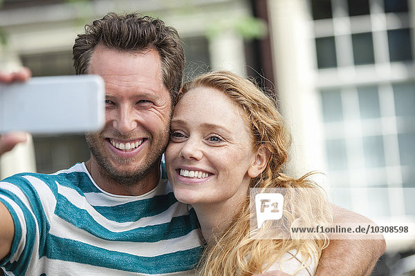Lächelndes Paar mit einem Selfie im Freien