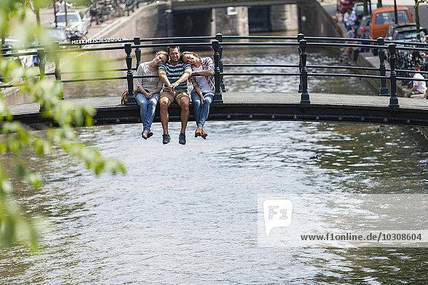 Niederlande  Amsterdam  drei glückliche Freunde sitzen auf der Brücke am Stadtkanal