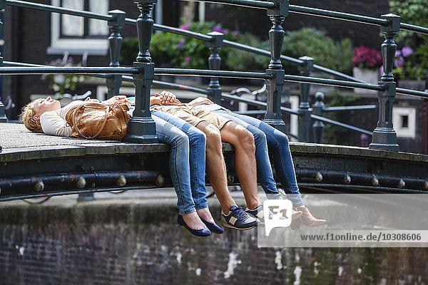Niederlande  Amsterdam  drei Freunde auf der Brücke liegend