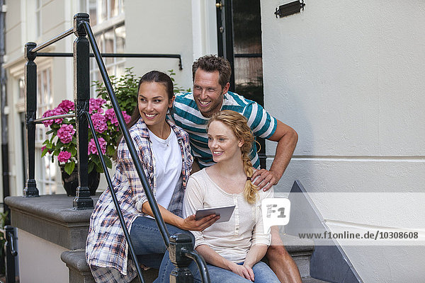 Netherlands  Amsterdam  three happy friends sitting with digital tablet at front door