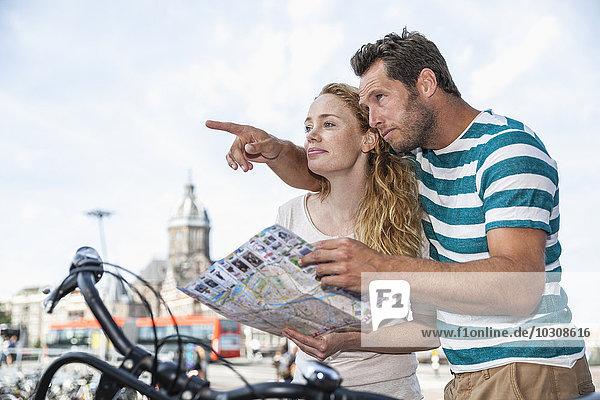 Niederlande  Amsterdam  Paar mit Karte sucht Richtung