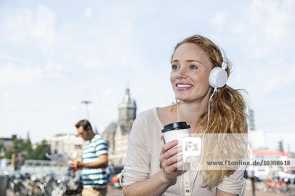 Niederlande  Amsterdam  lächelnde Frau mit Kopfhörer und Kaffee zum Mitnehmen in der Stadt